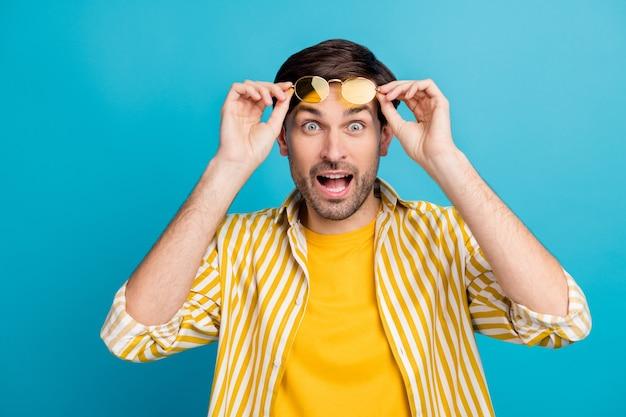 Zdjęcie szalonego zdumionego faceta widzi niesamowite zniżki na wakacje pod wrażeniem podnoszą nowoczesne jasne okulary noszą białe ubrania odizolowane na niebieskim tle