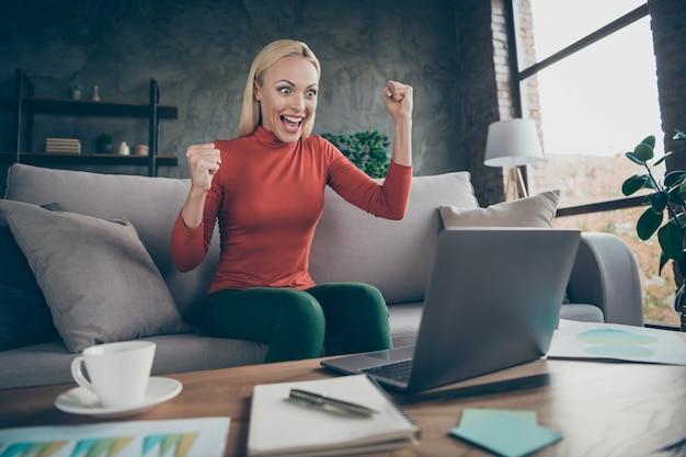 Zdjęcie szalonej blond kobiety biznesu wznoszącej pięści w górę, świętującej pierwszą inwestycję projekt startowy, ubranie freelancera na co dzień, pomarańczowy sweter, siedząca sofa, stół, notebook w pomieszczeniu