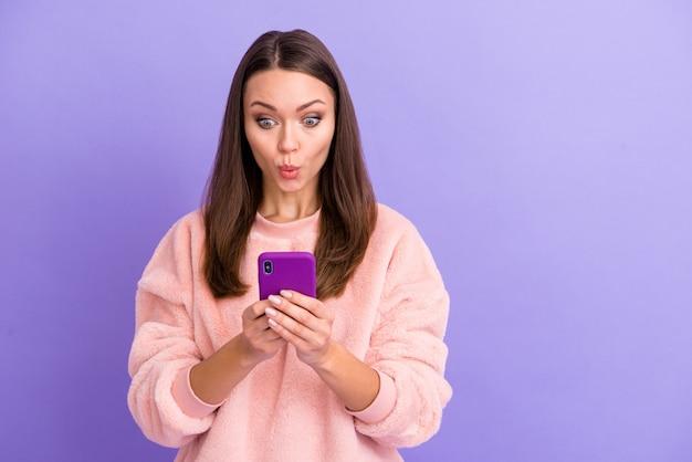 Zdjęcie szalonej, zabawnej blogerki trzymającej telefon w szoku na fioletowej ścianie