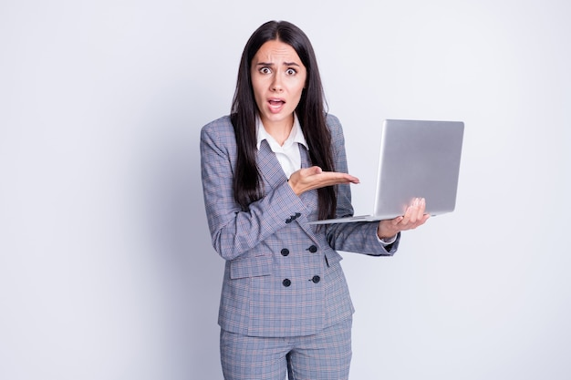 Zdjęcie szalonej zły biznes dama trzymaj notatnik netbook złe połączenie wifi internet niezadowolony straszny drogi dostawca rozłącz formalny strój w kratę odizolowany szary kolor tło