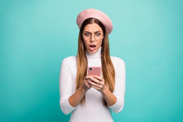 Zdjęcie szalonej zszokowanej pani przytrzymaj telefon czytanie nowego postu negatywne komentarze otwarte usta nosić specyfikacje nowoczesny różowy beret czapka biały golf na białym tle jasny turkusowy kolor tła