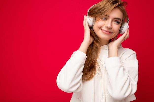 Zdjęcie szczęśliwa uśmiechnięta młoda blondynki kobieta ubrana w białą bluzę z kapturem na białym tle nad kolorowymi