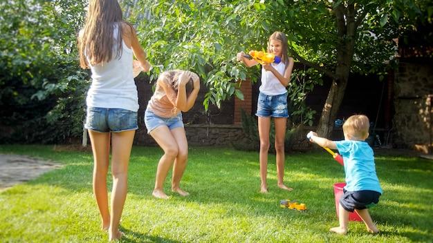 Zdjęcie szczęśliwe dzieci o walkę pistoletem na wodę w ogrodzie przydomowym domu. rodzinna zabawa i zabawa na świeżym powietrzu latem