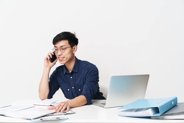 Zdjęcie szczęśliwego azjatyckiego mężczyzny w wieku 30 lat w okularach siedzącego przy stole i rozmawiającego na smartfonie podczas pracy w jasnym pokoju biurowym