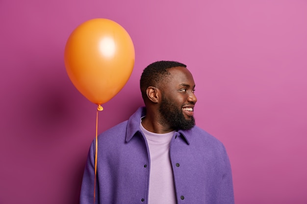 Zdjęcie szczęśliwego brodatego faceta odwraca się, zauważa kogoś po prawej, czeka dziewczyna z balonem w dłoni, uśmiecha się przyjaźnie