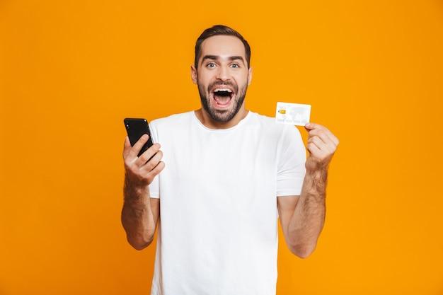 Zdjęcie szczęśliwego człowieka 30s w casual, trzymając smartfon i kartę kredytową, na białym tle