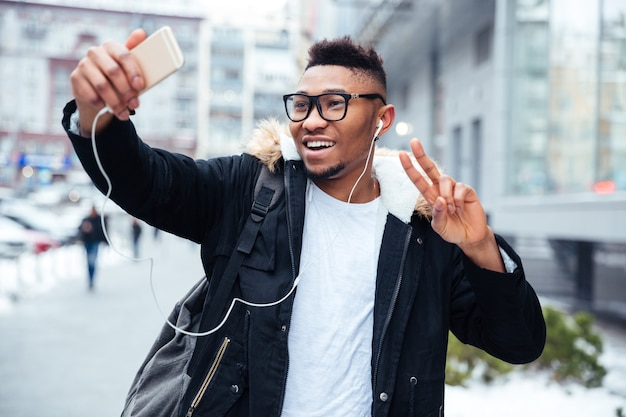 Zdjęcie szczęśliwego człowieka trzymającego telefon w rękach i zrób selfie z gestem pokoju podczas słuchania muzyki na zewnątrz.