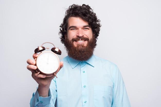 Zdjęcie szczęśliwego człowieka z brodą, pokazując budzik na białym tle.
