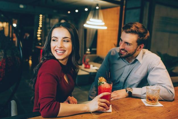 Zdjęcie szczęśliwego dziewczyny siedzącej z przystojnym facetem w barze. ona patrzy gdzieś na bok i uśmiecha się. młody człowiek też na nią patrzy i się uśmiecha.