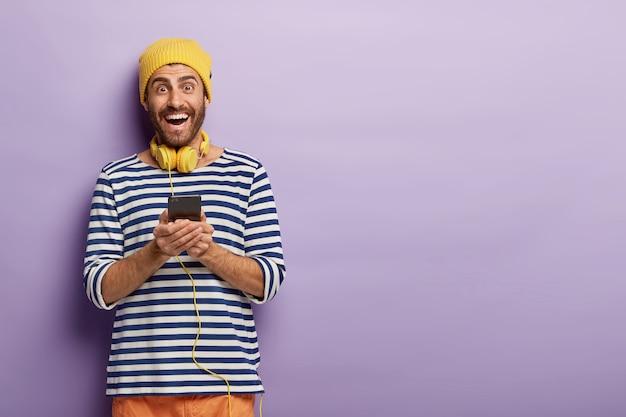Zdjęcie szczęśliwego, energetyzowanego, nieogolonego hipstera, który trzyma telefon komórkowy, cieszy się, że może pobrać nową aplikację, ma słuchawki stereo na szyi, nosi żółtą czapkę i sweter w paski