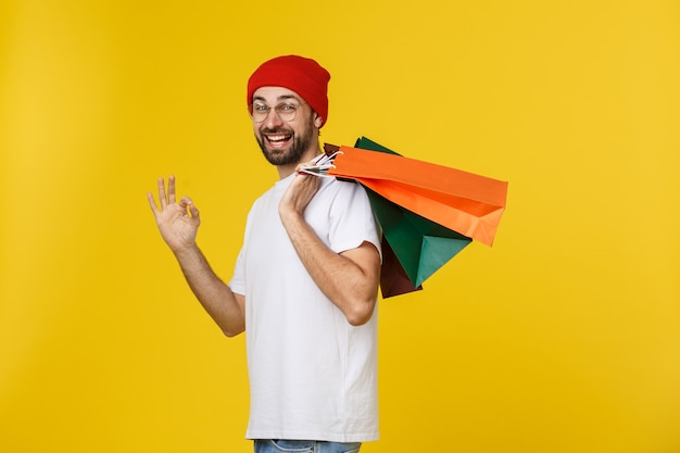 Zdjęcie szczęśliwego faceta, trzymając torby na zakupy, odizolowane na żółtej przestrzeni