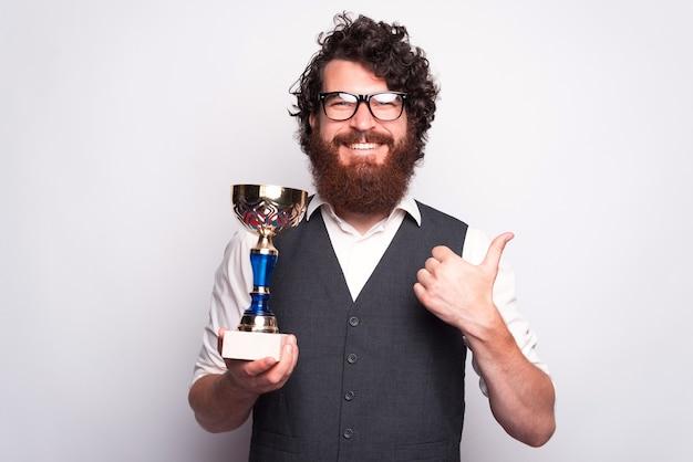 Zdjęcie szczęśliwego mężczyzny rasy kaukaskiej, który trzyma puchar i pokazuje kciuk do góry