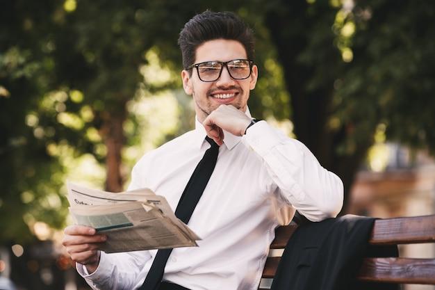 Zdjęcie szczęśliwego mężczyzny w garniturze siedzi na ławce w zielonym parku i czyta gazetę w słoneczny dzień