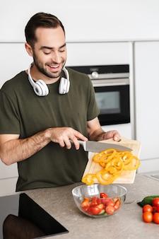Zdjęcie szczęśliwego młodego brodatego mężczyzny w pomieszczeniu w kuchni gotowanie sałatka jarzynowa zjeść śniadanie ze słuchawkami na szyi.