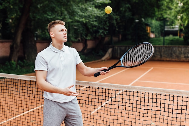 Zdjęcie szczęśliwego młodego człowieka w koszulce polo, niosąc rakietę tenisową i uśmiechając się stojąc na korcie tenisowym.