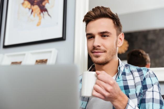 Zdjęcie szczęśliwego młodego mężczyzny ubranego w koszulę w nadruk klatki, siedzącego na kanapie w domu i korzystającego z laptopa