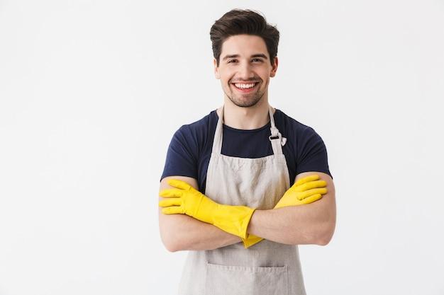 Zdjęcie szczęśliwego młodego mężczyzny w żółtych gumowych rękawiczkach do ochrony rąk uśmiechającego się podczas sprzątania domu na białym tle nad białym