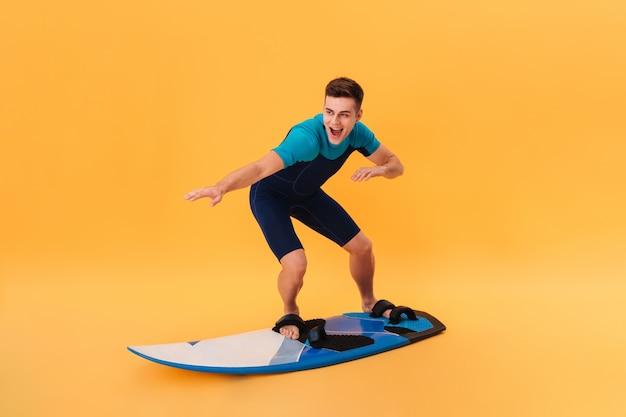 Zdjęcie szczęśliwego surfera w kombinezonie przy użyciu deski surfingowej jak na fali