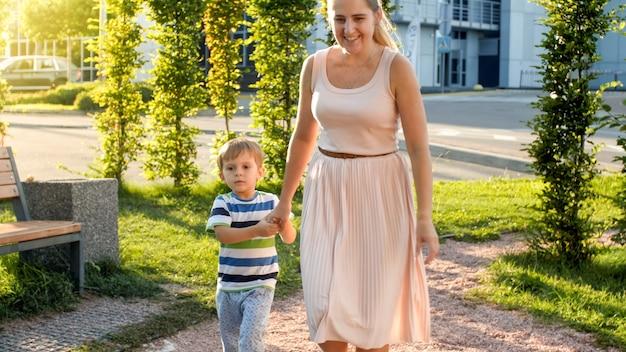Zdjęcie szczęśliwego wesołego małego chłopca z młodą matką spacerującą i biegającą na placu zabaw w parku