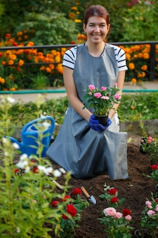 Zdjęcie szczęśliwej brunetki agronom trzymającej różowe róże w ogrodzie