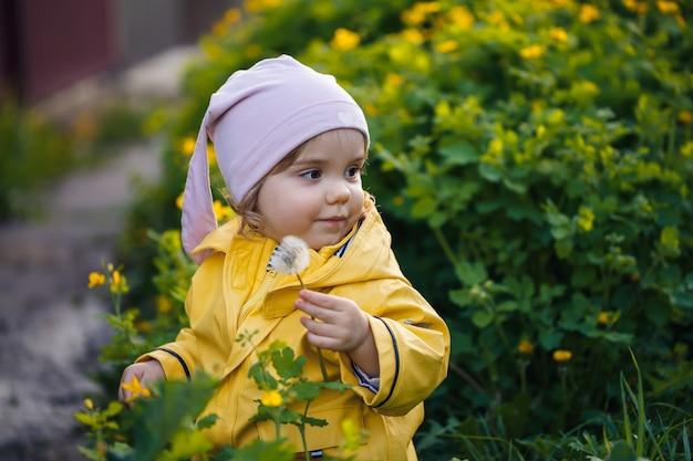 Zdjęcie szczęśliwej dziewczynki w żółtej kurtce i białym kapeluszu bawiącej się na łące, w otoczeniu kwiatów i trawy, bawiącej się na polu podczas zachodu słońca. koncepcja dzieciństwa.