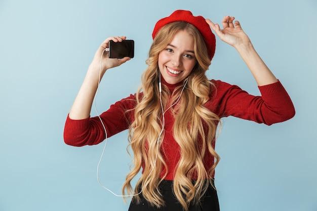 Zdjęcie szczęśliwej dziewczyny 20s noszących słuchawki do słuchania muzyki na telefonie komórkowym na białym tle