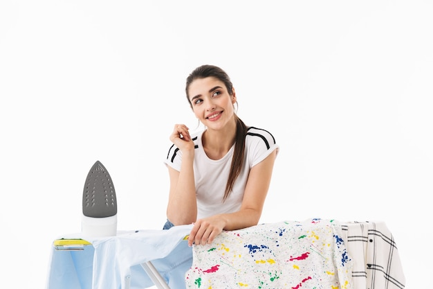 Zdjęcie szczęśliwej kobiety gospodyni domowej w wieku 20 lat ubranej w odzież casual, prasowanie czystych ubrań na desce odizolowanej nad białą ścianą