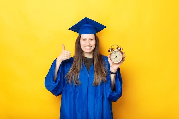 Zdjęcie szczęśliwej kobiety kończącej studia pokazując kciuk do góry i budzik na żółtym tle