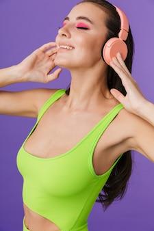 Zdjęcie szczęśliwej kobiety mody ubranej w chudy kombinezon ze słuchawkami i uśmiechniętej