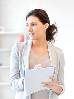 Zdjęcie szczęśliwej kobiety z dużym notatnikiem