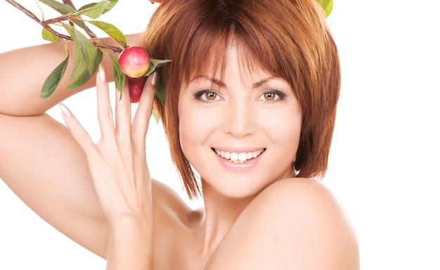 Zdjęcie szczęśliwej kobiety z gałązką jabłka