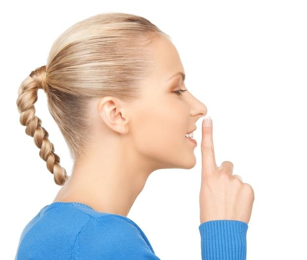Zdjęcie szczęśliwej kobiety z palcem na ustach