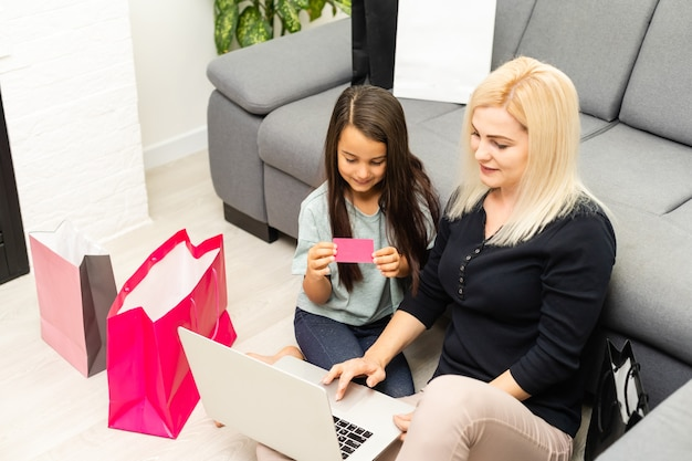 Zdjęcie szczęśliwej matki i dziecka z laptopem, zakupy online