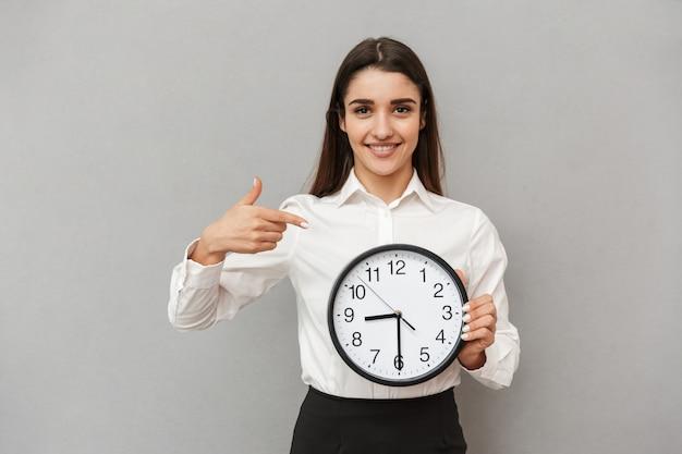 Zdjęcie szczęśliwej młodej kobiety w białej koszuli i czarnej spódnicy, wskazując palcem na duży okrągły zegar, trzymając w ręku, odizolowane na szarej ścianie