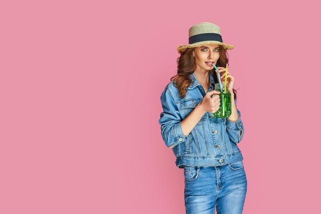 Zdjęcie szczęśliwej młodej kobiety w dżinsowych ubraniach i letnim słomkowym kapeluszu ma dobry nastrój na tle pastelowego różu