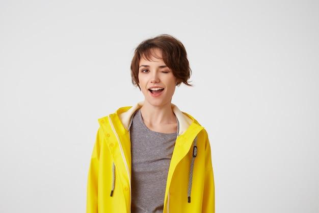 Zdjęcie szczęśliwej młodej ładnej kobiety w żółtym płaszczu przeciwdeszczowym, ciesz się życiem, patrzy w kamerę z pozytywnymi minami i figlarnymi mrugnięciami, szeroko uśmiechając się na białej ścianie.
