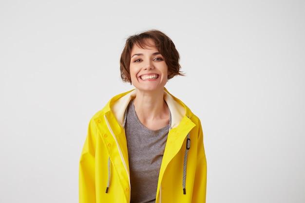 Zdjęcie szczęśliwej młodej ładnej kobiety w żółtym płaszczu przeciwdeszczowym, ciesz się życiem, patrzy w kamerę z pozytywnymi minami, szeroko uśmiechając się na białej ścianie.