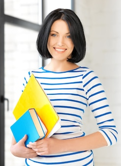 Zdjęcie szczęśliwej nastolatki z książkami i folderami