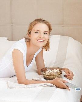 Zdjęcie szczęśliwej nastolatki z pilotem do telewizora i popcornem