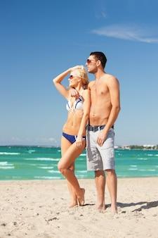 Zdjęcie szczęśliwej pary w okularach przeciwsłonecznych na plaży (skup się na kobiecie)