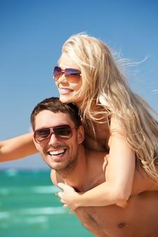 Zdjęcie szczęśliwej pary w okularach przeciwsłonecznych na plaży (skup się na mężczyźnie)
