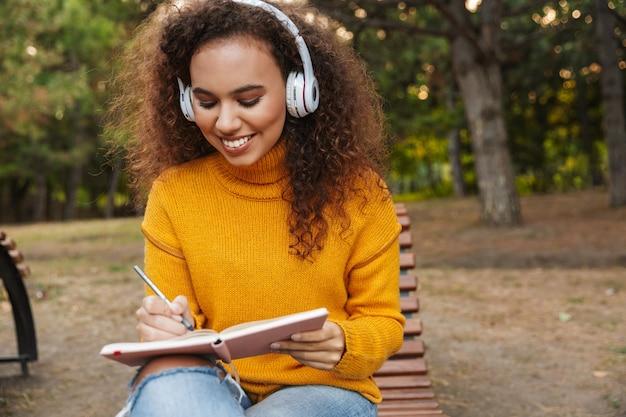 Zdjęcie szczęśliwej pięknej młodej kobiety kręcone siedzieć na ławce w parku na zewnątrz słuchania muzyki w słuchawkach pisania notatek w notesie.