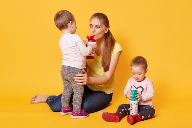 Zdjęcie szczęśliwej rodziny, mamy z jej uroczymi bliźniakami