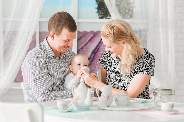 Zdjęcie szczęśliwej rodziny siedzącej z synkiem przy stole