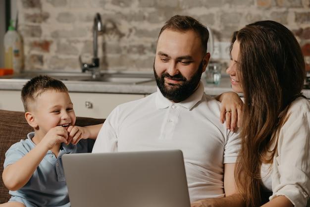 Zdjęcie szczęśliwej rodziny z bliska uśmiechnięty ojciec pracuje zdalnie na laptopie, podczas gdy jego szczęśliwy syn i żona wpatrują się w ekran