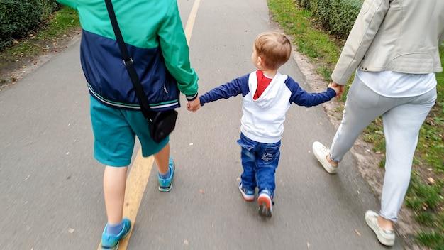 Zdjęcie szczęśliwej rodziny z małym chłopcem trzymającym się za ręce i spacerującym po parku