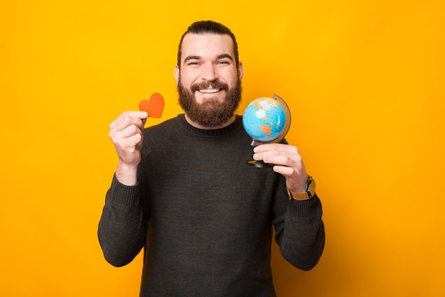 Zdjęcie szczęśliwy brodaty przystojny mężczyzna trzymający kulę ziemską i czerwone serce