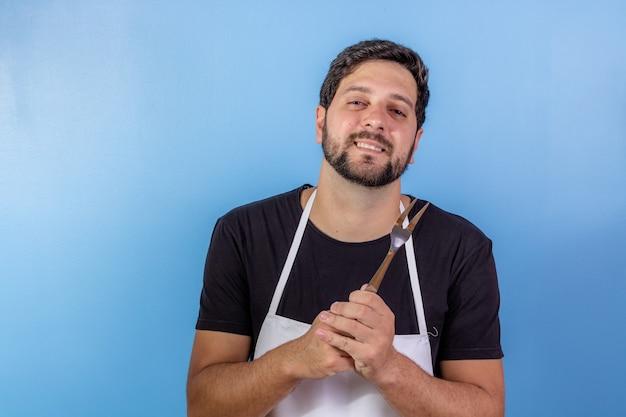 Zdjęcie szczęśliwy człowiek szefa kuchni trzymając naczynie do gotowania mięsa