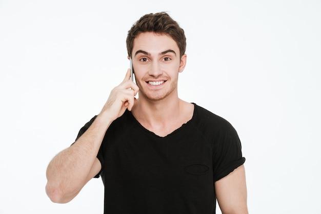 Zdjęcie szczęśliwy młody człowiek ubrany w czarny t-shirt stojący na białym tle rozmawia przez telefon.