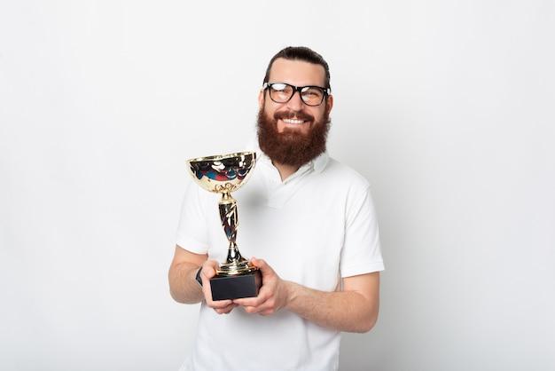 Zdjęcie szczęśliwy wesoły młody brodaty mężczyzna w białej koszulce trzyma puchar mistrza